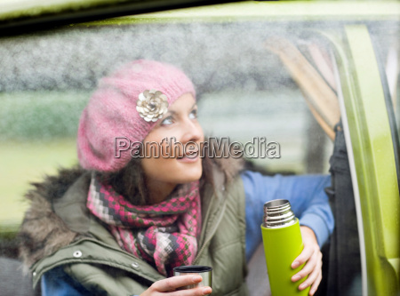 woman enjoying hot drink from flask