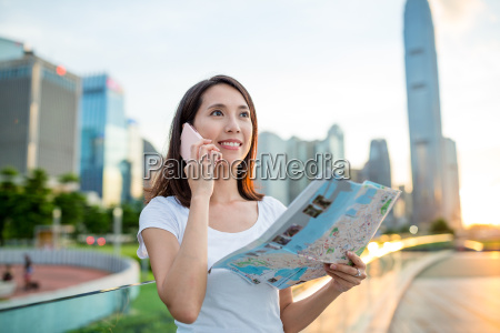 woman using city map and calling