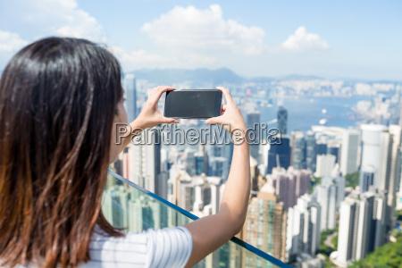 woman taking photo of hong kong