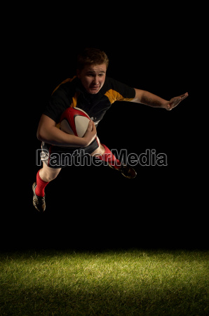 rugby player mid air with ball