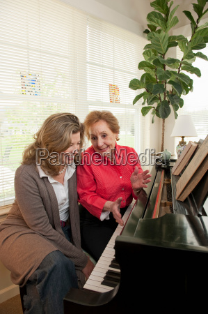 mother and daughter talking at piano