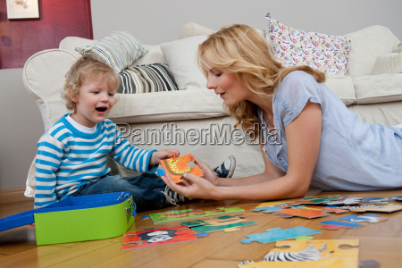 woman playing on floor with son