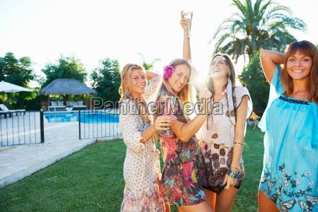 girls celebrating with drinks by pool