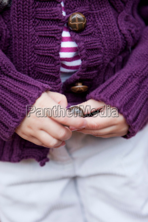 young girls hands knitted sweater