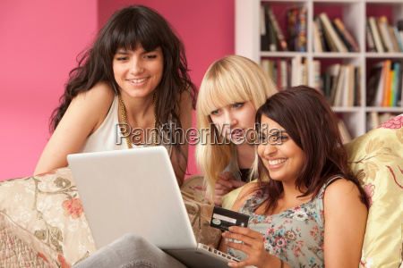 three young women shopping on computer