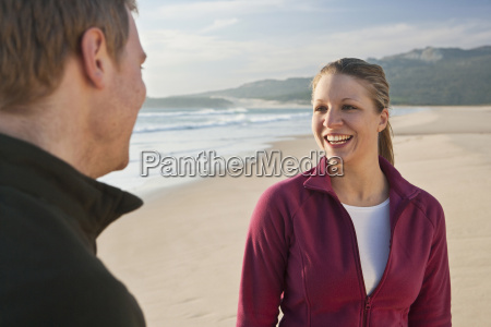 young couple smiling on beach