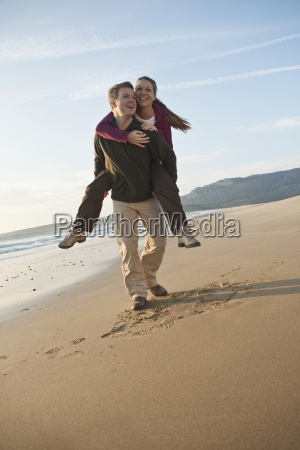 young man giving woman piggyback ride