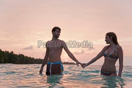 couple holding hands in water at