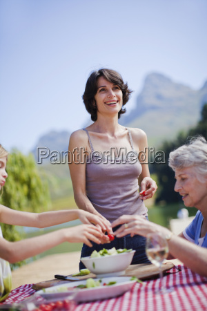 mother making picnic lunch at table