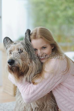 smiling woman hugging dog at home