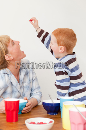 mother and son playing at table