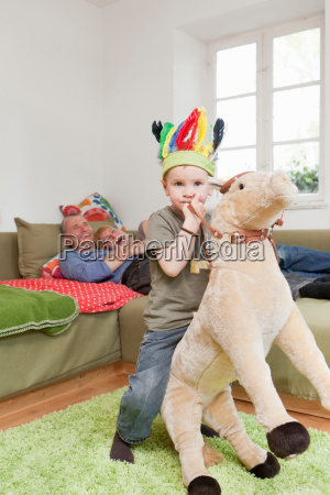 boy in war bonnet playing with