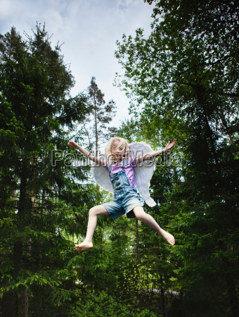 girl wearing wings and jumping in