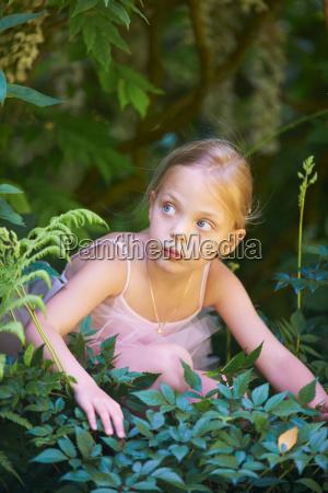 girl in ballet costume hiding in