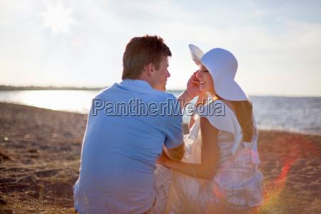 newlywed couple sitting on beach