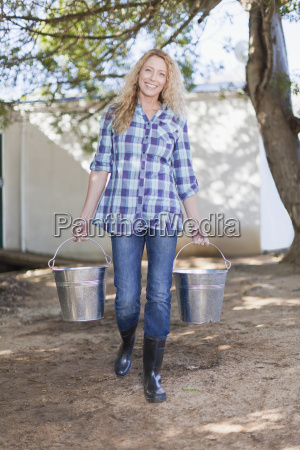 smiling woman carrying pails outdoors
