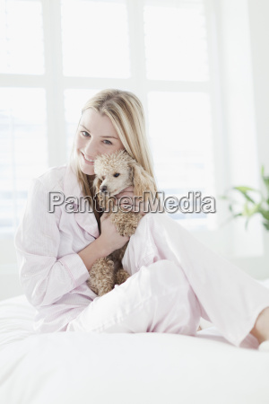 smiling woman hugging dog on bed