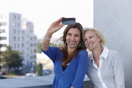 women taking picture on balcony