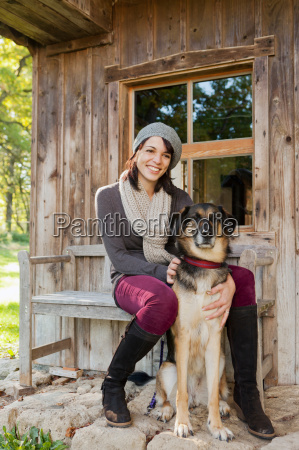 woman petting dog on porch