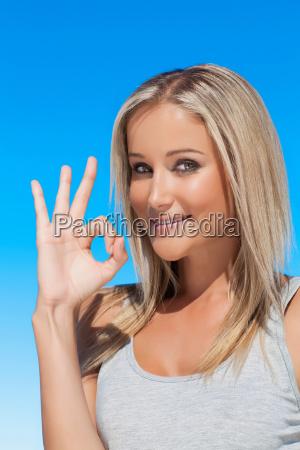 smiling woman making ok sign