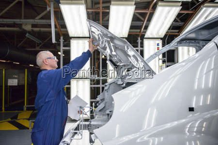 worker inspecting paint finish of vehicle