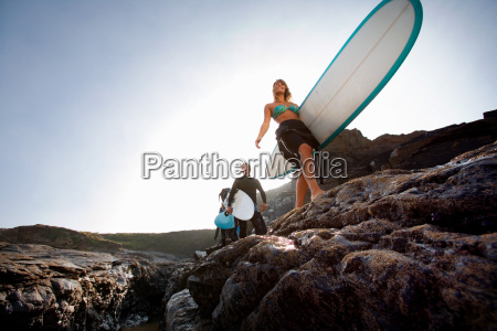 three people carrying surfboards
