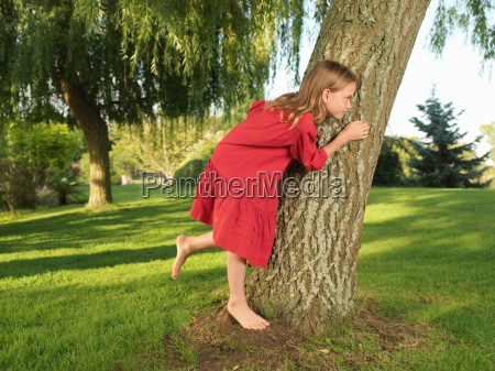 young girl hiding behind tree