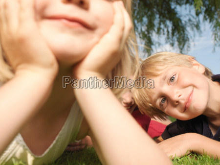 young children lying on grass close