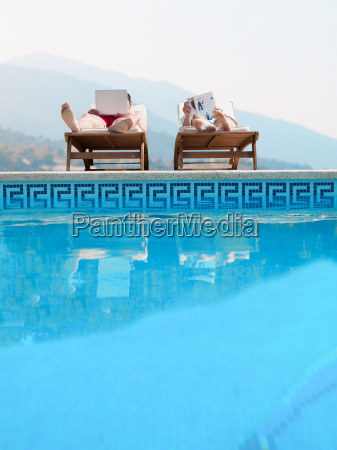 couple sunbathing by swimming pool