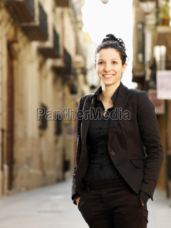young woman standing in street smiling