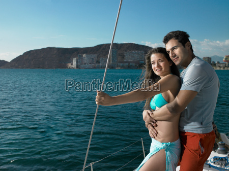 young couple standing on yacht smiling