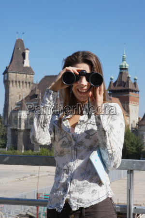 woman looking through binoculars smiling