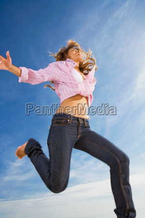 woman jumping in the air smiling