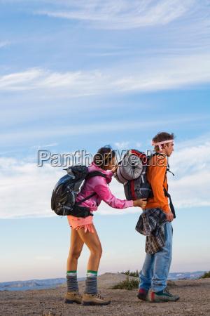 woman adjusting mans backpack