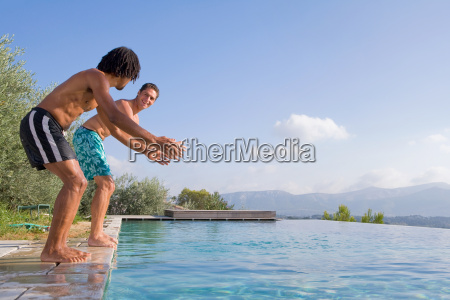 young men diving into a pool