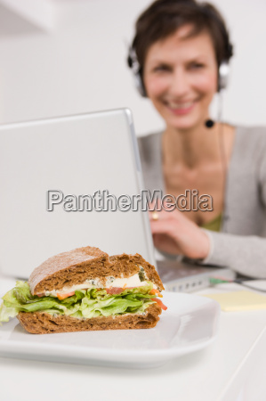 woman with headset behind a sandwich