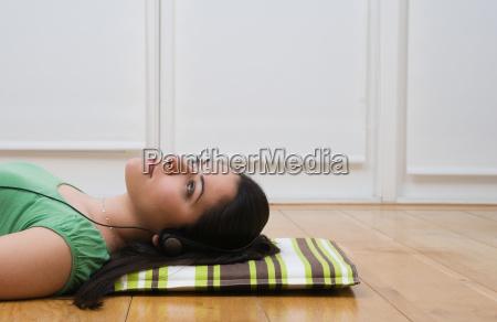 woman lying on floor listening to