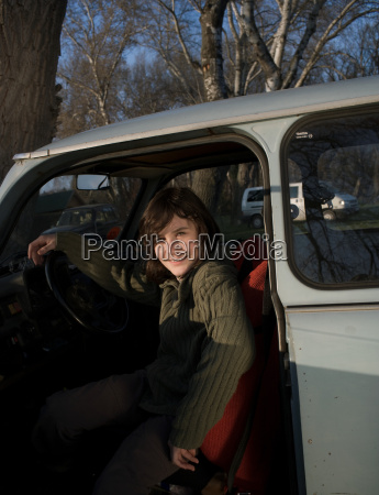 boy in drivers seat of car