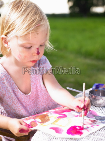 little girl painting in a green