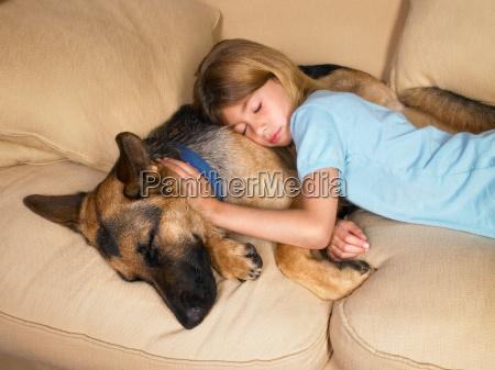 young girl sleeping on her dog