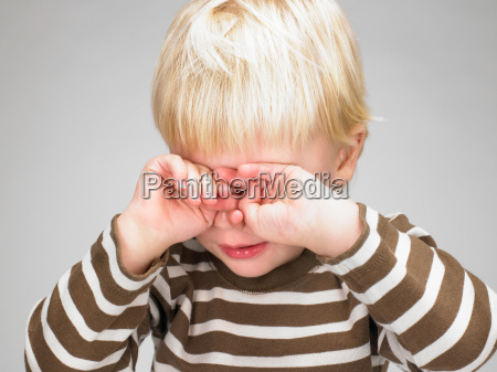 little boy covering his eyes