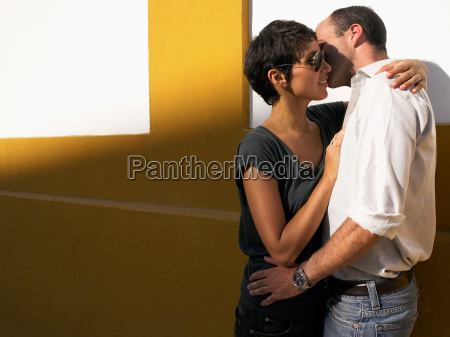 couple kissing up against a wall