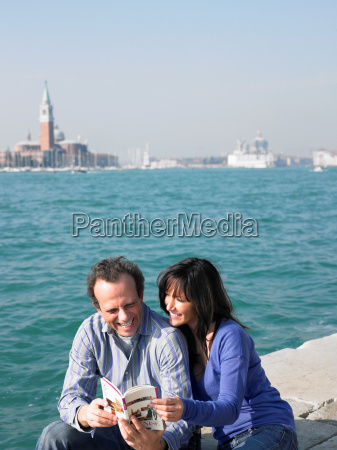 couple sitting looking at guide book