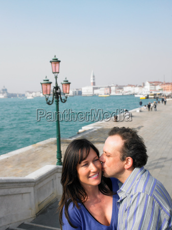 portrait of kissing couple near lagoon