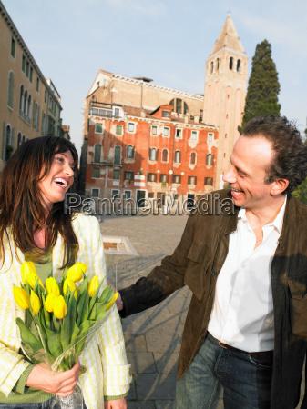 couple walking woman holding flowers