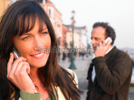 man and woman using mobile phones