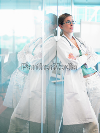 female doctor leaning on glass wall