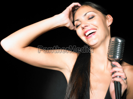 woman laughing holding microphone