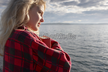 young woman by sea cuddling book