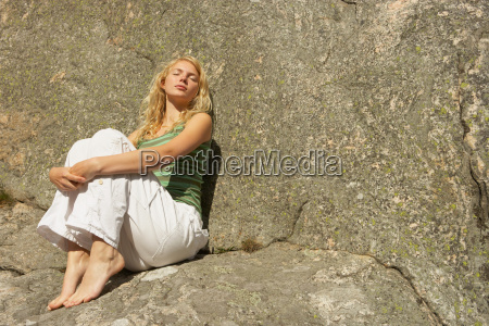 young woman sitting on rocks
